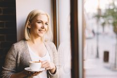 Mujer con una taza de café que hace una pausa la ventana Imágenes de archivo libres de regalías