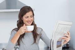 Mujer con una taza de café que lee un periódico Fotografía de archivo