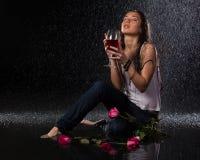 Mujer con y vidrio de vino bajo la lluvia. Fotografía de archivo libre de regalías