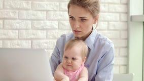 Mujer concentrada con el bebé que trabaja en el ordenador portátil Funcionamiento de la mujer de negocios almacen de video