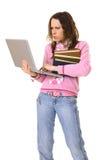 Mujer concentrada con la computadora portátil y la pila de libros Imágenes de archivo libres de regalías
