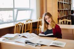 Mujer concentrada del estudiante que se sienta en el escritorio en libros que estudian viejos de la biblioteca de universidad y q Fotografía de archivo