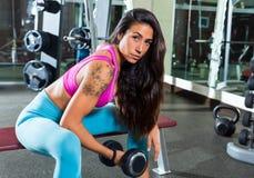 Mujer concentrada pesa de gimnasia de la muchacha del rizo del bíceps Fotos de archivo libres de regalías