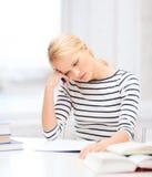 Mujer concentrada que estudia en universidad Imagen de archivo
