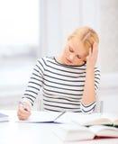 Mujer concentrada que estudia en universidad Fotos de archivo