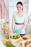 Mujer concentrada que prepara la ensalada en la cocina Foto de archivo