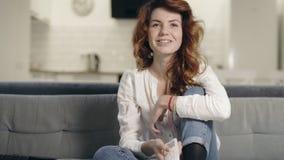 Mujer concentrada que se sienta en el sofá en la cocina Muchacha emocionada del primer que ve la TV almacen de metraje de vídeo