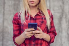 Mujer concentrada, tranquila que mecanografía y que consigue mensajes en su smartphone El SMS de la ojeada del influencer de Inte fotos de archivo libres de regalías