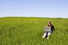 Mujer conectada en la hierba Fotografía de archivo libre de regalías