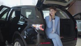 Mujer confiada con el pelo corto en el traje formal azul clásico que se sienta en tronco de coche abierto que habla por el teléfo almacen de metraje de vídeo