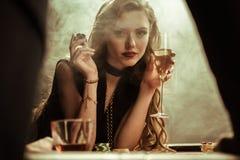 Mujer confiada con la bebida y ficha de póker en manos fotografía de archivo
