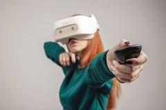 Mujer confiada del pelirrojo que lleva las auriculares de la realidad virtual, apuntando del arco foto de archivo libre de regalías