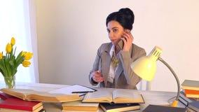 Mujer confiada en administrador de oficinas experto de las gafas con los documentos de papel metrajes