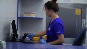 Mujer confiada en uniforme azul y los guantes de goma que ponen el estante para los tubos de ensayo en el refrigerador especial c almacen de metraje de vídeo