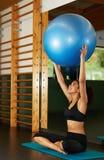Mujer confiada joven que sostiene la bola de Pilates que parece tan feliz Foto de archivo libre de regalías