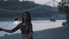 Mujer confiada linda de la tolerancia que realiza una demostración con la llama que se coloca en el bosque o el parque Demostraci almacen de metraje de vídeo