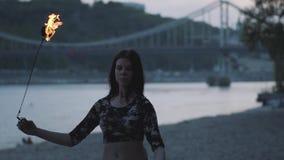 Mujer confiada linda de la tolerancia que realiza una demostración con la llama que se coloca en el bosque o el parque Demostraci metrajes