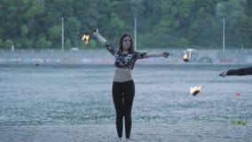 Mujer confiada linda que realiza una demostración con la llama que se coloca en el bosque o el parque Demostración experta del ar metrajes