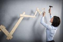 Mujer confiada que construye el gráfico positivo de la tendencia con el martillo a disposición Imagen de archivo libre de regalías