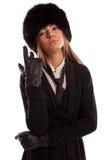 Mujer confiada que lleva un sombrero de piel negro, un lazo negro y un cuero g Fotografía de archivo