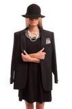 Mujer confiada que lleva un sombrero negro, una chaqueta y un vestido con la perla Imagenes de archivo