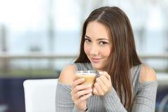 Mujer confiada que presenta sosteniendo una taza de café Foto de archivo libre de regalías
