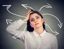 Mujer confusa con muchas flechas torcidas que salen de su cabeza Imágenes de archivo libres de regalías