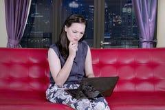 Mujer confusa con un ordenador portátil en el apartamento Imagenes de archivo