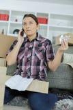 Mujer confusa preocupante en los muebles de junta del teléfono Fotos de archivo libres de regalías