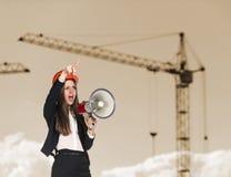 Mujer-constructor en el casco de protección que grita Imagenes de archivo