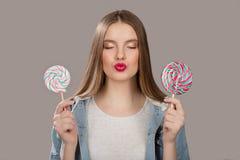 Mujer contenta con la piruleta colorida grande El concepto de dulces imagenes de archivo