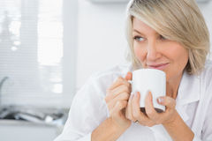 Mujer contenta que come café en la mañana Imagenes de archivo
