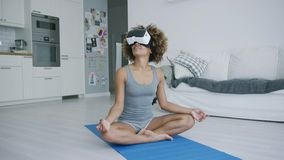 Mujer contenta que medita en vidrios de VR metrajes