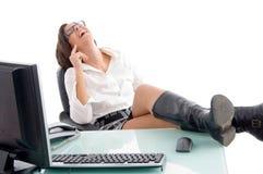 Mujer contenta que se sienta en oficina Imágenes de archivo libres de regalías
