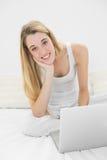 Mujer contenta que sonríe en la cámara usando su cuaderno que se sienta en su cama Fotos de archivo libres de regalías