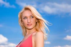 Mujer contra un cielo azul con las nubes Imagen de archivo