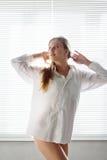Mujer contra una persiana fotos de archivo