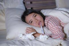 Mujer coreana asiática cansada y enferma hermosa joven que miente en el enfermo de la cama en casa que sufre la sensación fría de fotos de archivo libres de regalías