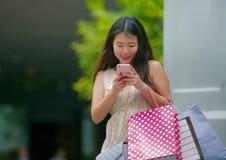 Mujer coreana asiática feliz y hermosa joven que camina en los panieres que llevan de la calle usando el teléfono móvil que busca foto de archivo