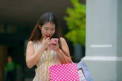 Mujer coreana asiática feliz y hermosa joven que camina en los panieres que llevan de la calle usando el teléfono móvil que busca fotos de archivo