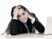 Mujer corporativa del negocio desesperada y abrumada con el ordenador portátil imagenes de archivo
