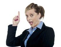 Mujer corporativa impactante que señala hacia arriba Foto de archivo libre de regalías