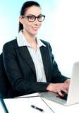 Mujer corporativa que pulsa en la computadora portátil Fotografía de archivo libre de regalías