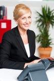 Mujer corporativa sonriente en oficina fotografía de archivo