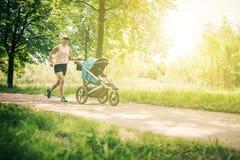 Mujer corriente con el cochecito de bebé que disfruta de verano en parque imágenes de archivo libres de regalías