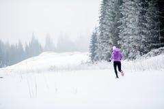Mujer corriente del invierno, inspiración que activa y motivación foto de archivo