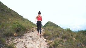 Mujer corriente en el camino de la montaña Muchacha del deporte que ejercita afuera en montañas almacen de video