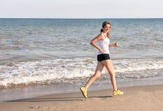 Mujer corriente Mujer activa del deporte que corre cerca de wat Foto de archivo