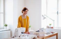 Mujer creativa joven en un estudio, inicio del pequeño negocio de adaptación foto de archivo