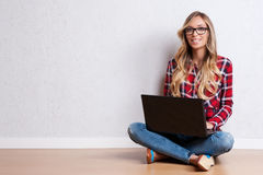 Mujer creativa joven que se sienta en el piso con el ordenador portátil / B casual Fotografía de archivo libre de regalías